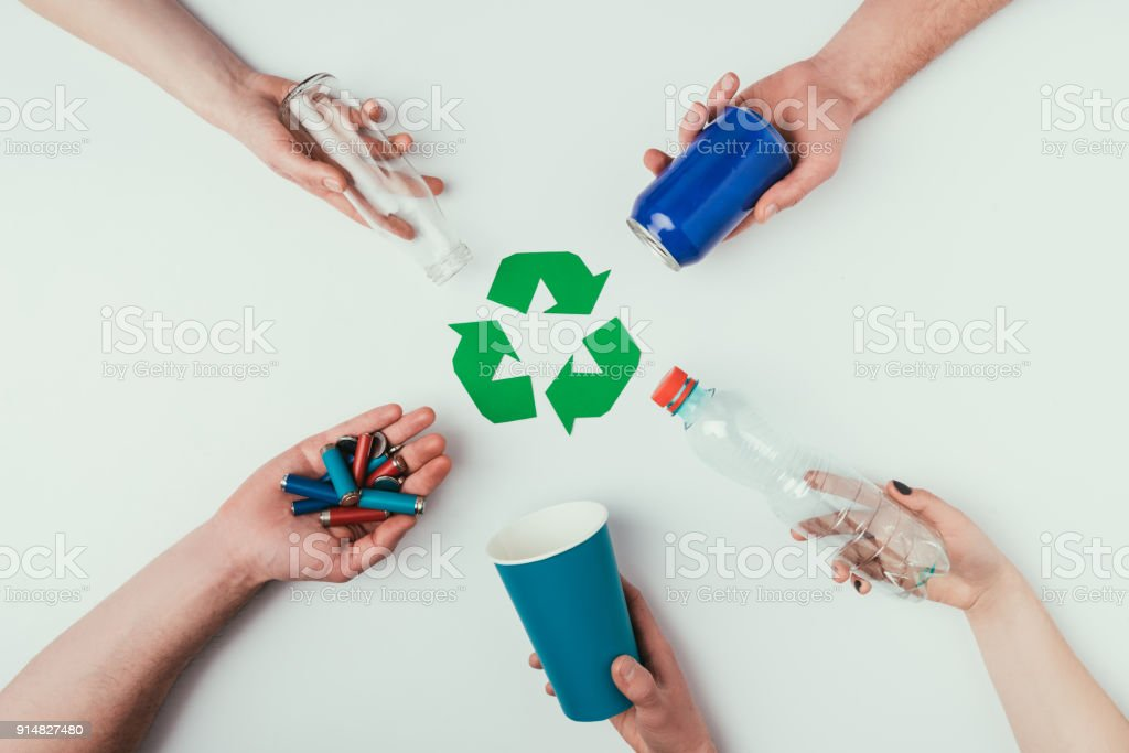partial view of people showing various types of garbage around recycle sign isolated on grey royalty-free stock photo