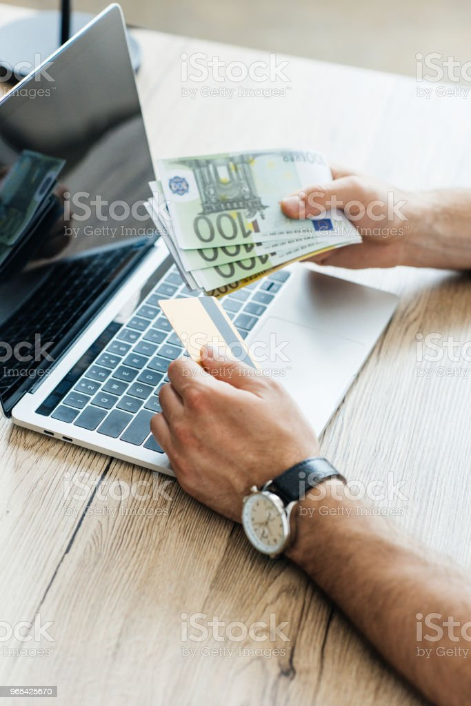 partial view of person holding credit card and euro banknotes at workplace with laptop zbiór zdjęć royalty-free
