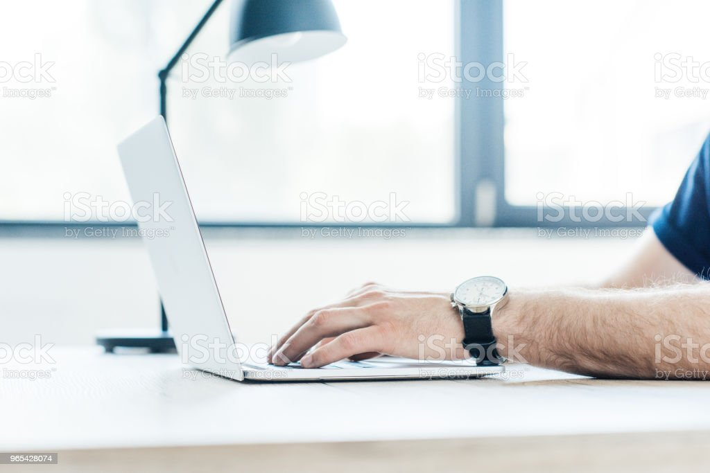 partial view of person using laptop at workplace zbiór zdjęć royalty-free