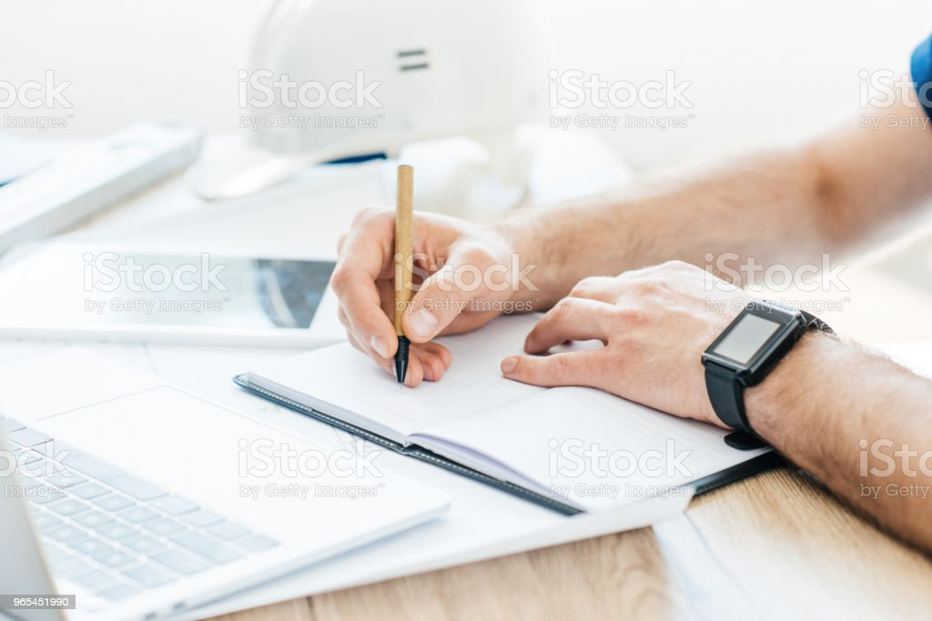 partial view of person wearing smartwatch and taking notes at workplace royalty-free stock photo