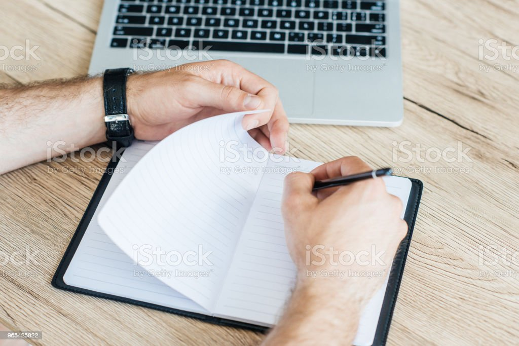 partial view of person writing in notebook at wooden table royalty-free stock photo