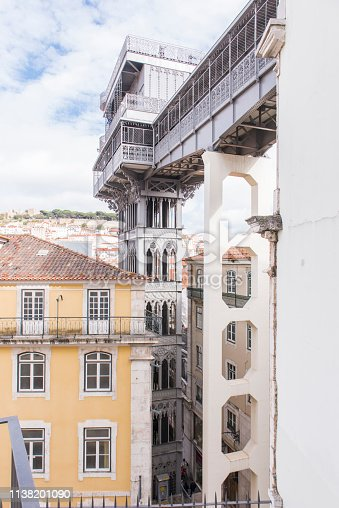 Partial view of Santa Justa elevator at central Lisbon city, Portugal. In the background on the top of the hill the Saint George Castle (Castelo Sao Jorge).