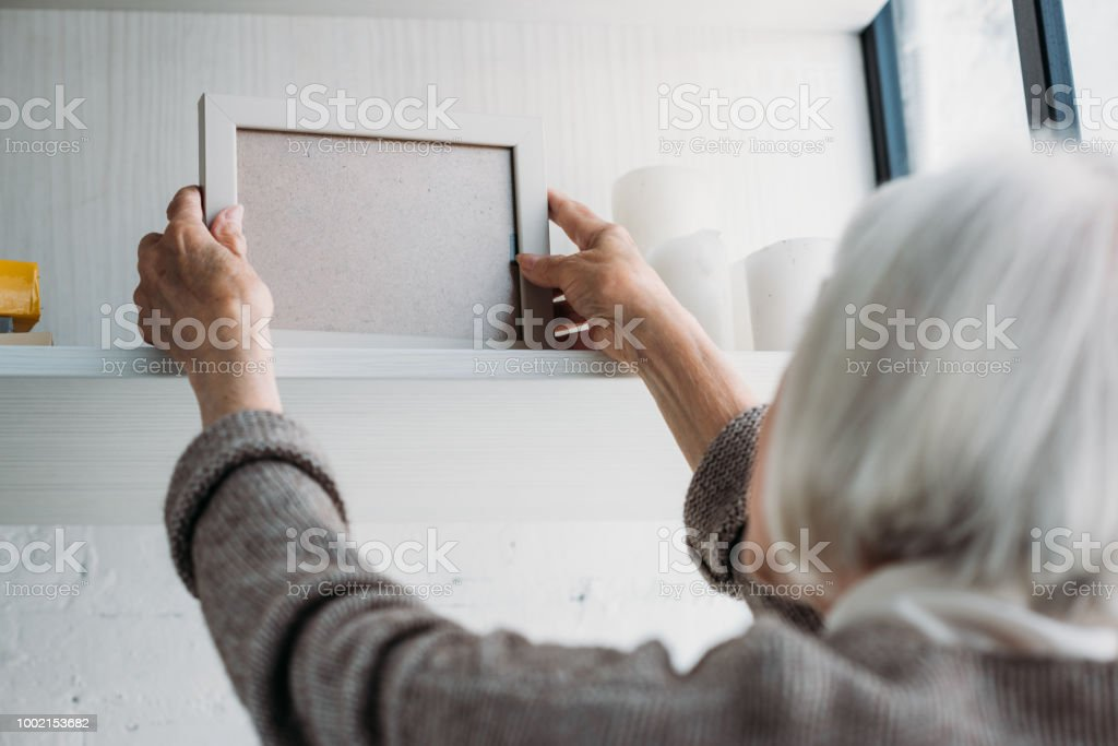 partial view of senior lady taking empty photo frame from bookshelf at home stock photo