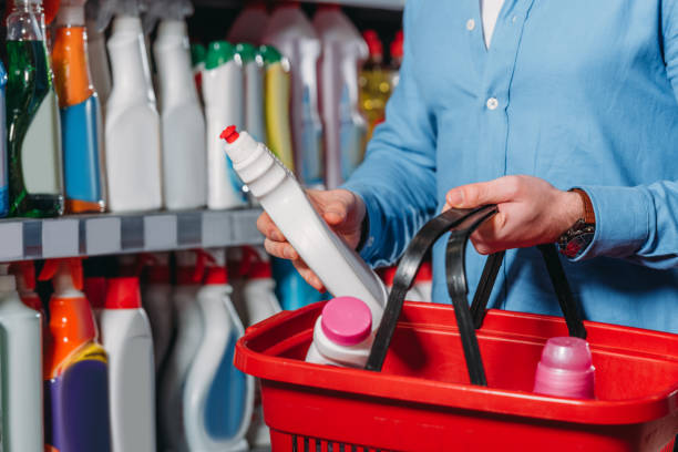 partial view of shopper putting detergent into shopping basket in supermarket - disinfectant stock pictures, royalty-free photos & images