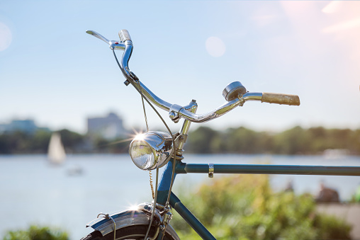 partial view of vintage blue bicycle with handlebar and light under blue summer sky
