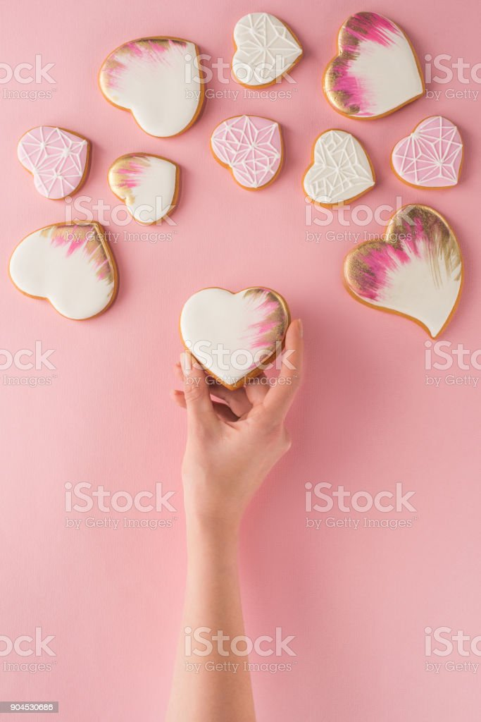 partial view of woman holding glazed cookie in hand isolated on pink, st valentines day concept stock photo