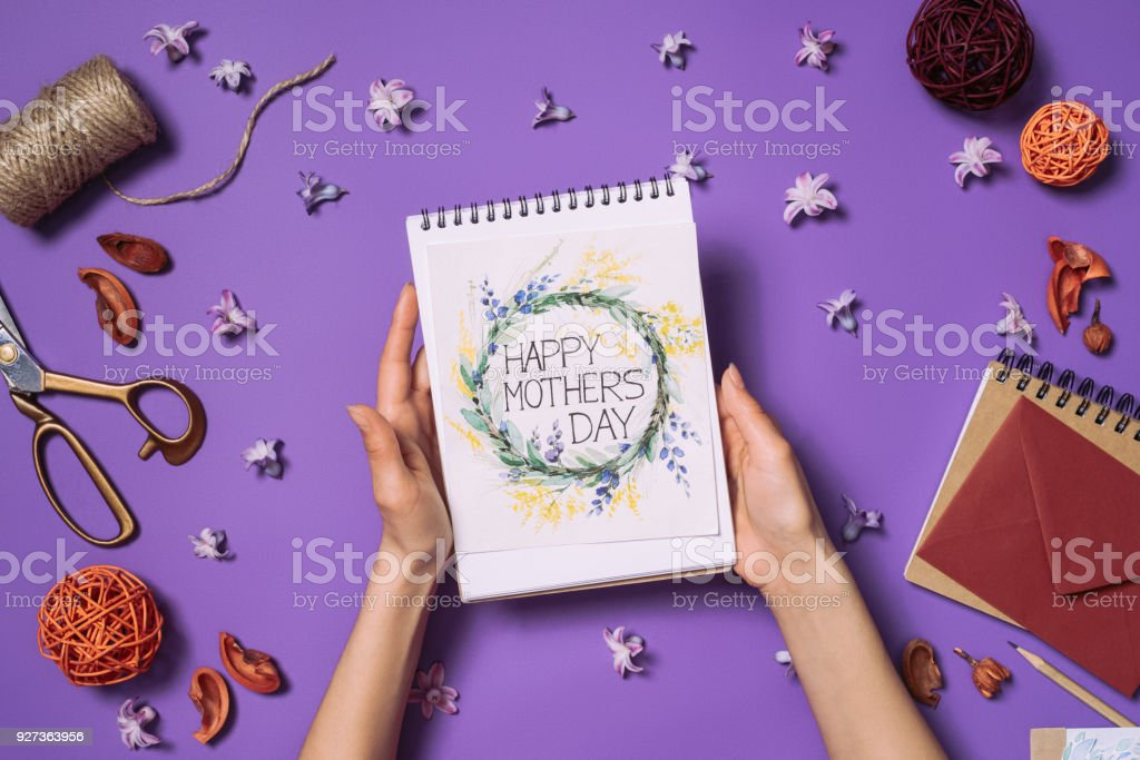 partial view of woman holding happy mothers day postcard in hands with decorations around isolated on purple partial view of woman holding happy mothers day postcard in hands with decorations around isolated on purple Adult Stock Photo
