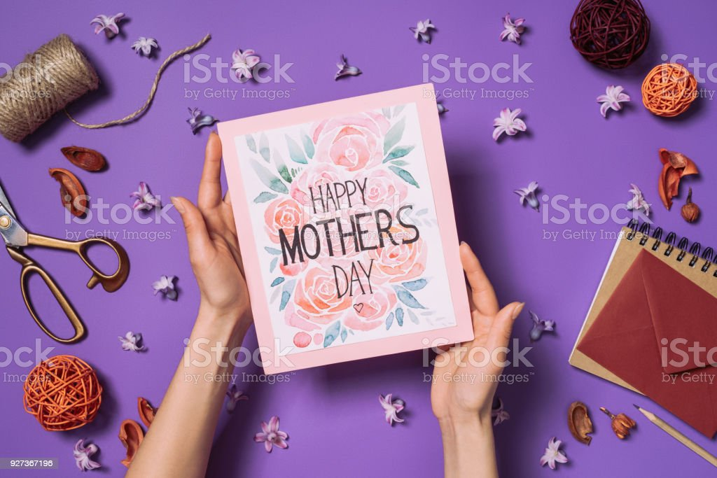 partial view of woman holding happy mothers day postcard in hands with decorations around isolated on purple - Royalty-free Adult Stock Photo