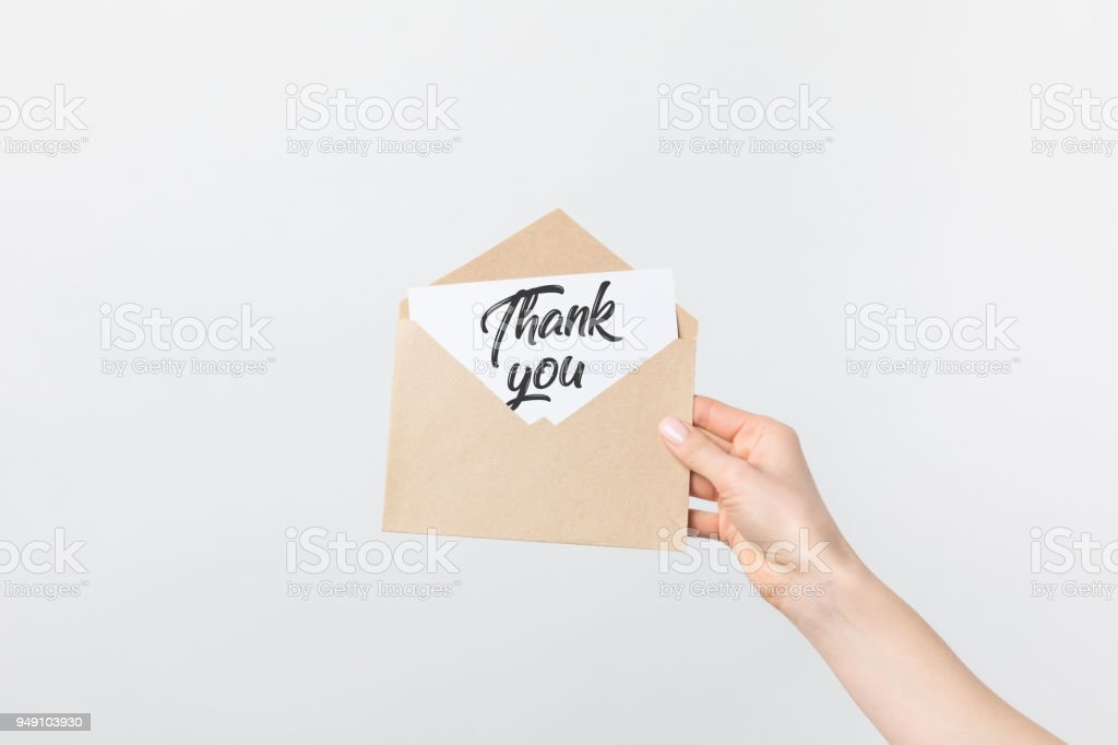 partial view of woman holding kraft envelope with thank you card isolated on white stock photo