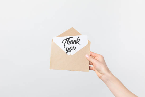 partial view of woman holding kraft envelope with thank you card isolated on white - thank you stock pictures, royalty-free photos & images