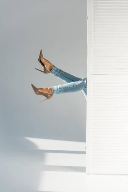 partielle ansicht der frau in jeans und hochhackigen schuhen auf grauem hintergrund - raumteiler weiß stock-fotos und bilder
