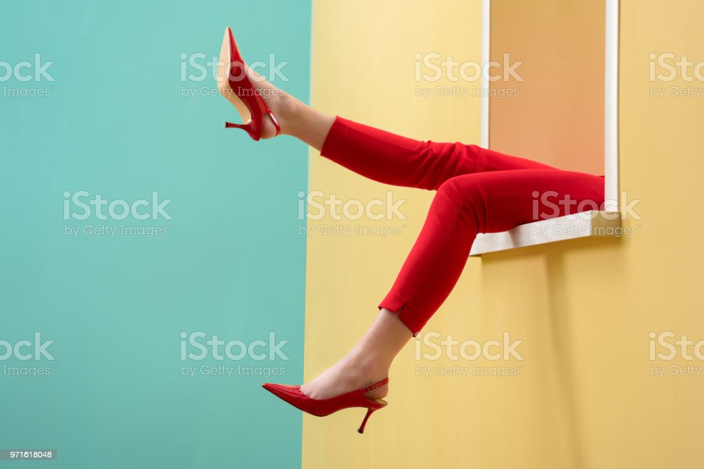 partial view of woman in red pants and shoes outstretching legs out decorative window royalty-free stock photo