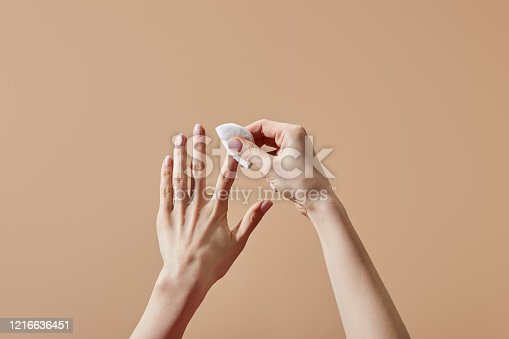 Partial view of woman removing nail polish with cotton pad isolated on beige