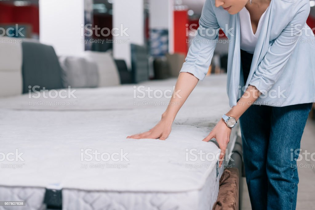 partial view of woman touching orthopedic mattress in furniture shop stock photo