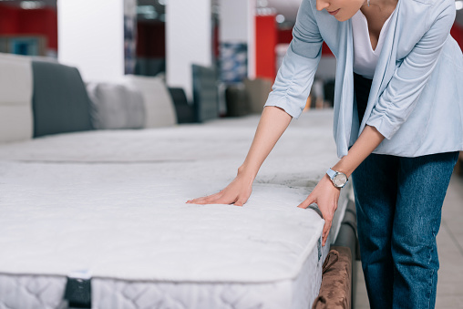 Partial View Of Woman Touching Orthopedic Mattress In Furniture Shop Stock Photo - Download Image Now