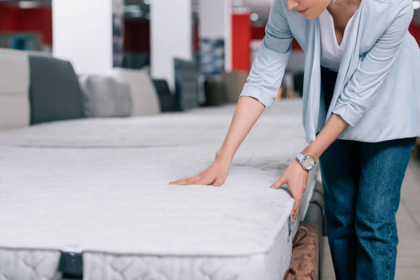 partial view of woman touching orthopedic mattress in furniture shop - furniture shopping stock photos and pictures