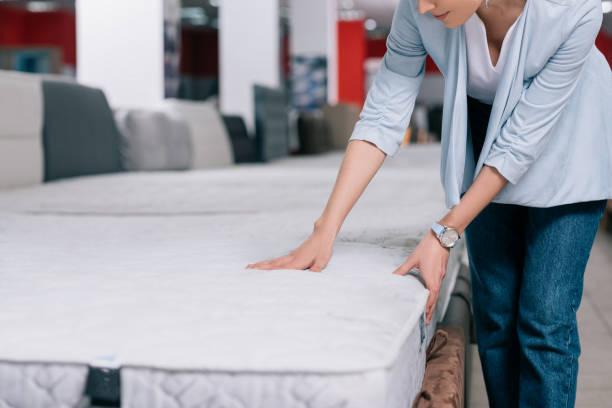mobilya mağazasında ortopedik yatak dokunmadan kadının kısmi görünümü - yatak stok fotoğraflar ve resimler