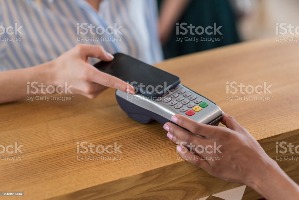 partial view of woman using smartphone for payment in cafe stock photo