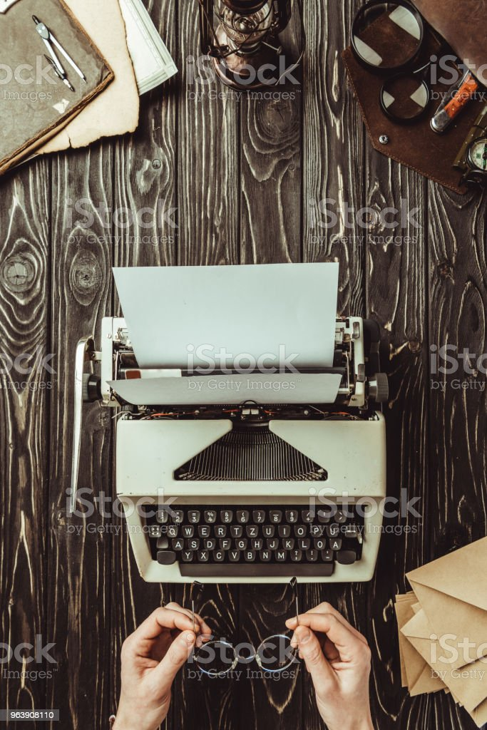 partial view of woman with eyeglasses, typing machine and envelopes on wooden tabletop - Royalty-free Adult Stock Photo
