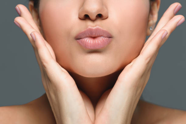 partial view of woman with hands at cheeks and duck face isolated on grey partial view of woman with hands at cheeks and duck face isolated on grey puckering stock pictures, royalty-free photos & images