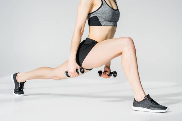 vista parcial do treinamento atlético novo da mulher com dumbbells no cinza - parte inferior - fotografias e filmes do acervo