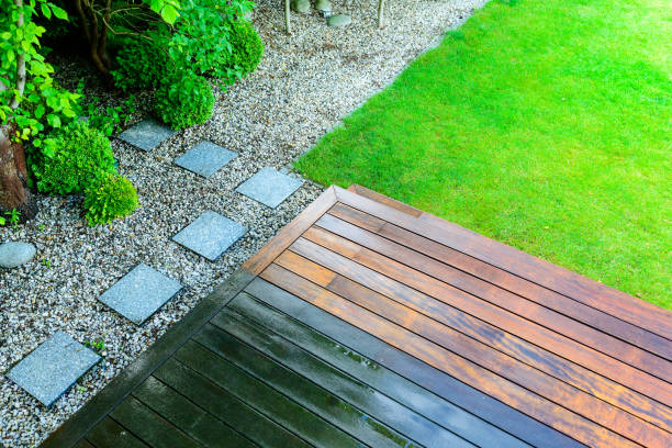 partially cleaned wooden terrace with a pressure washer by the green lawn stock photo