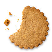 Partially eaten round gingerbread biscuit isolated on white from above. Serrated edge.