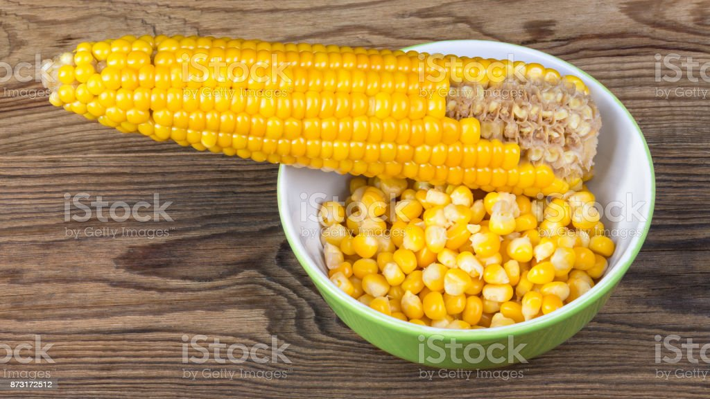 Partially empty corncob and heap of boiled maize. HD ratio 16x9 stock photo