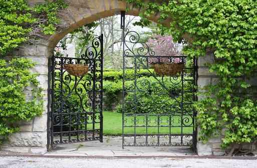 A partially open gate, entrance to a garden