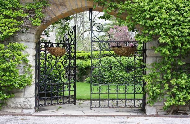 a partially open gate leading into a garden - grind bildbanksfoton och bilder