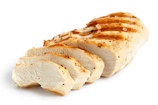Partially sliced grilled chicken breast with black pepper. Partially sliced grilled chicken breast with black pepper and rock salt isolated on white. chopped food stock pictures, royalty-free photos & images