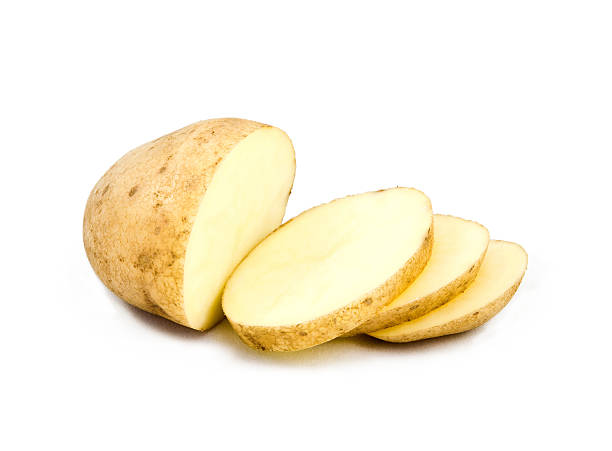 A partially sliced potato on white stock photo