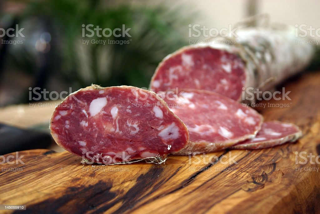 Partially sliced salami on wood stock photo