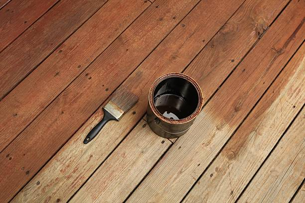 partially stained deck; paint brush and a can of stain - houtbeits stockfoto's en -beelden