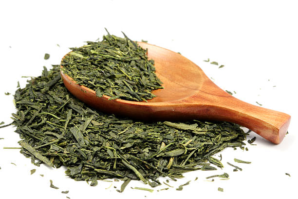 Partially-filled wooden spoon laying on loose green tea stock photo