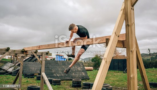 Male participant in a obstacle course doing irish table obstacle