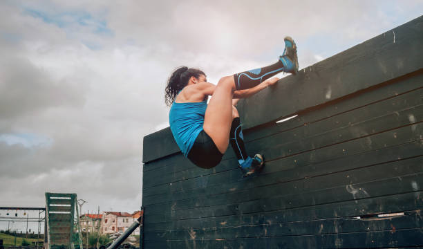 Participant in obstacle course climbing wall Female participant in an obstacle course climbing a wall obstacle course stock pictures, royalty-free photos & images