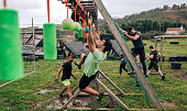 Male participant in an obstacle course doing suspension ring exercises