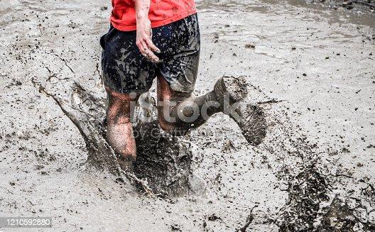 A participant of a physically demanding run, runs through the mud