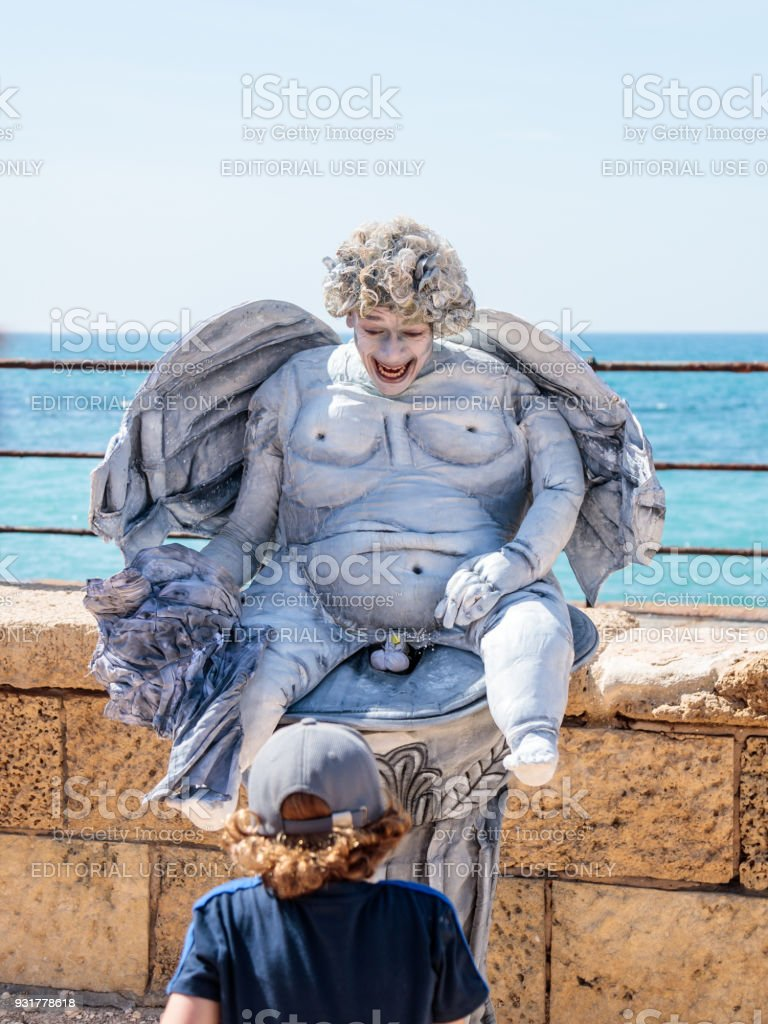 A participant of the Purim festival dressed as a statue sitting in a column and shows performance in ruins of old city Caesarea, Israel stock photo