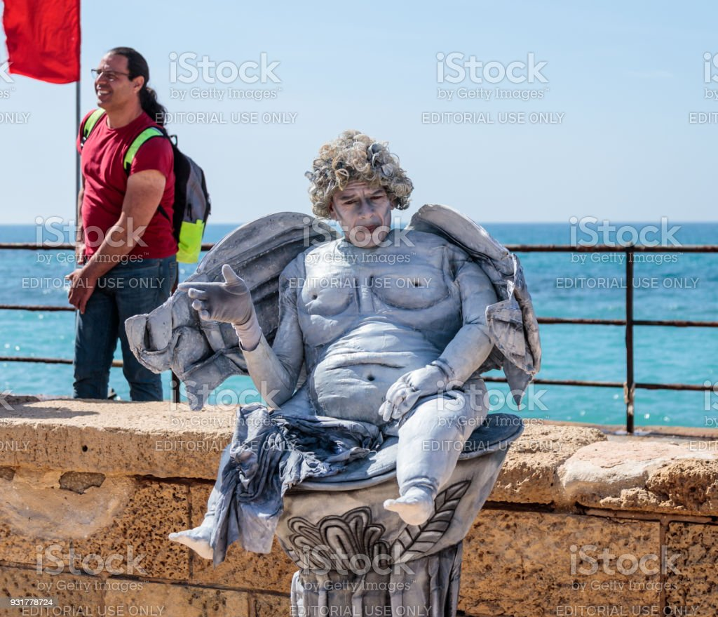 A participant of the Purim festival dressed as a statue sitting in a column in ruins of old city Caesarea, Israel stock photo