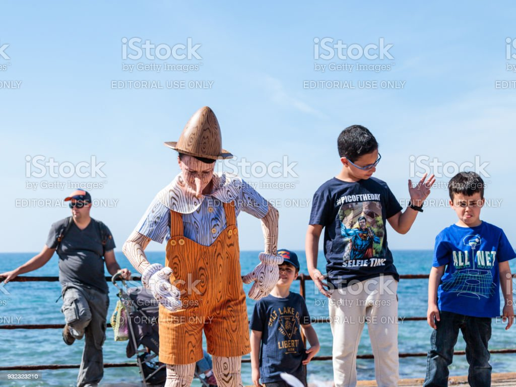 A participant of the Purim festival dressed in Pinocchio costume and visitor participate in the show in Caesarea, Israel stock photo