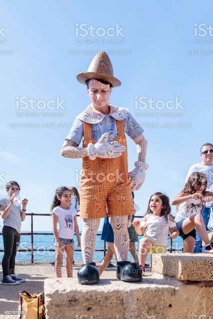 A participant of the Purim festival dressed in Pinocchio costume participates in the show in Caesarea, Israel stock photo