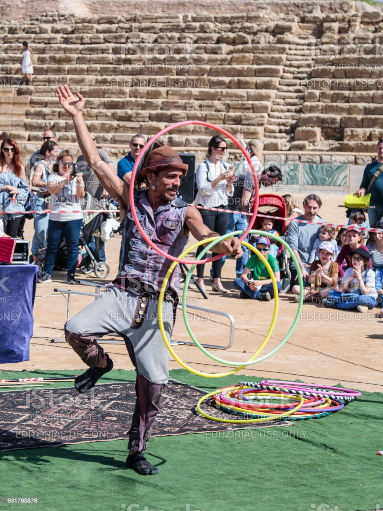 A participant of the Purim festival juggles with hoops for visitors in ruins of old city Caesarea, Israel stock photo