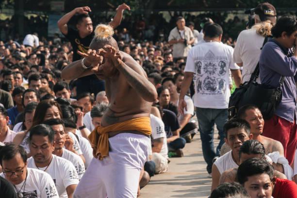 ein teilnehmer des sak yant festivals fällt in trance - buddhist tattoos stock-fotos und bilder