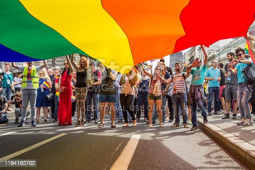 Picture of a people, gay pride participants, standing and waiving a giant rainbow flag, symbol of the homosexual struggle, during the 2016 edition of the Belgrade gay pride in Serbia. The pride was held on the 18th of September, it was the second consecutive edition without clashes, after several years of prohibition, and other years where huge fights opposed demonstrators, policemen and anti-homosexual activists.