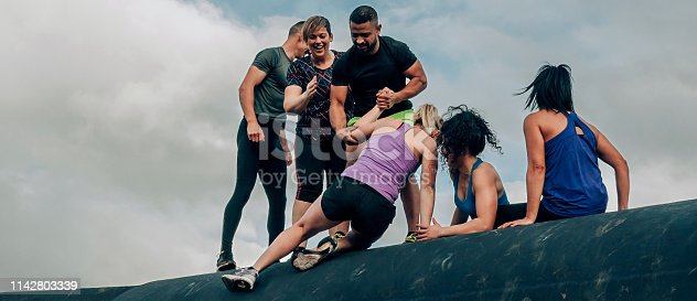 istock Participants in obstacle course climbing a drum 1142803339