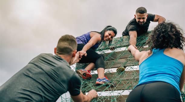 teilnehmer am hindernisparcours klettern netz - hindernisse überwinden stock-fotos und bilder