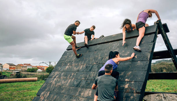 Participants in obstacle course climbing pyramid obstacle Group of participants in an obstacle course climbing a pyramid obstacle obstacle course stock pictures, royalty-free photos & images