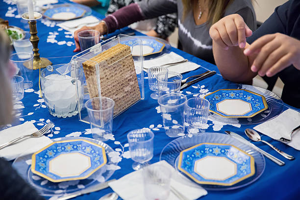 Participating in a traditional Passover seder Participating in a seder at a table set for a traditional Passover seder. RM passover stock pictures, royalty-free photos & images
